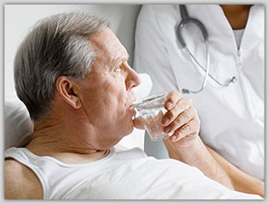 Nurse tending to elderly man as he lays in bed and sips water