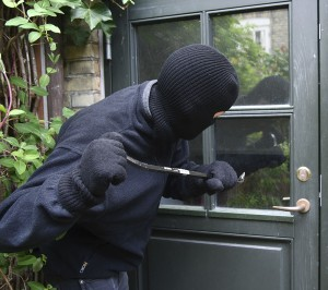 Robber attempting to break window of a door with a crowbar.